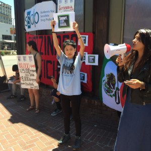 """A young woman holds a sign that says """"Support. Don't Punish"""" with others holding signs and one person with a megaphone. """"Support. Don't Punish"""" Global Day of Action at UC Berkeley in 2016"""
