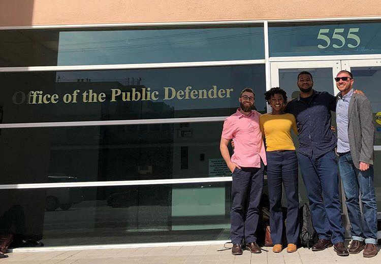 Four Golden Gate University School of Law Students stand in front of Office of Public Defender