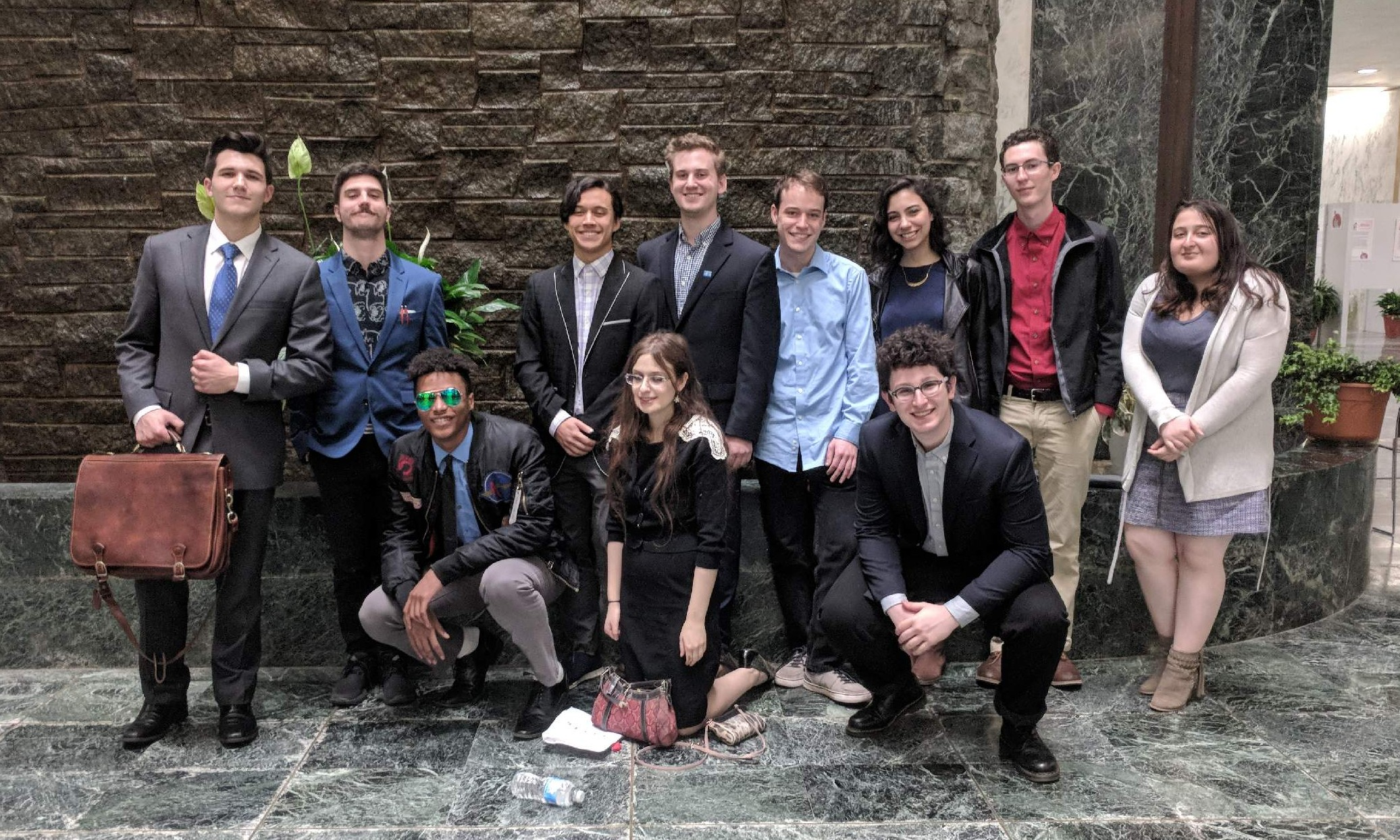 Eleven New York state SSDP students dressed in business attire smiling and standing together in the lobby of the New York State legislative office building
