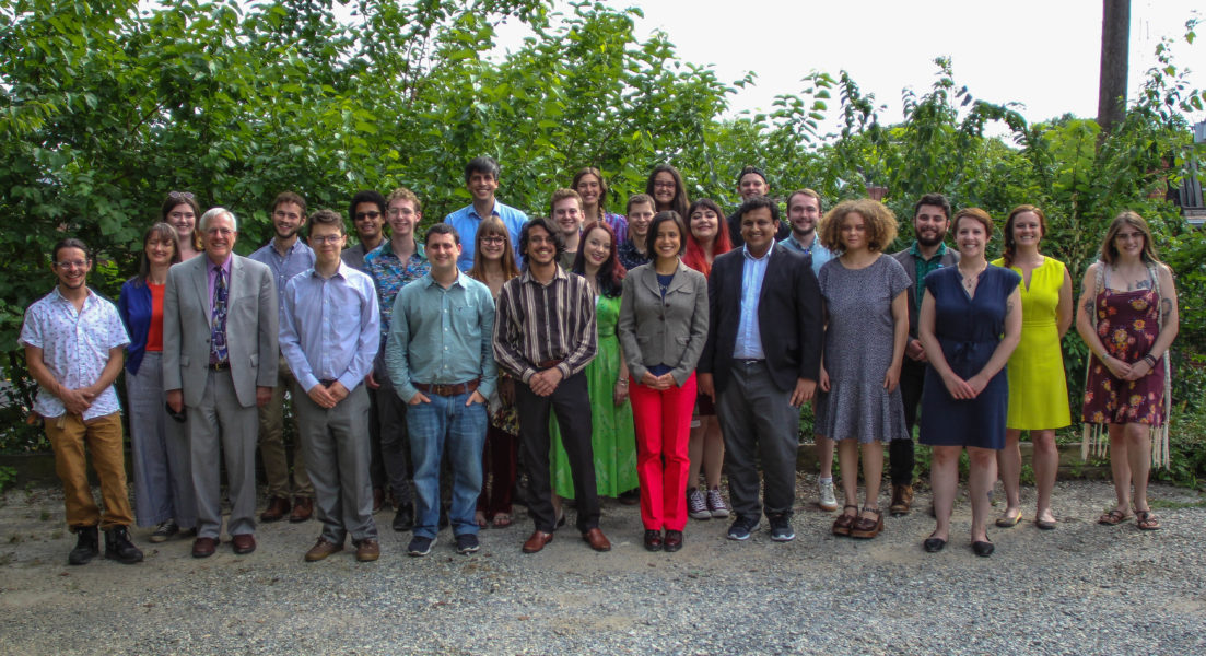 SSDP staff, board, students and alumni (about 30 people standing in rows, smiling) during the 2019 SSDP Strategy Summit - roughly 30 people smiling, standing in rows in front of trees