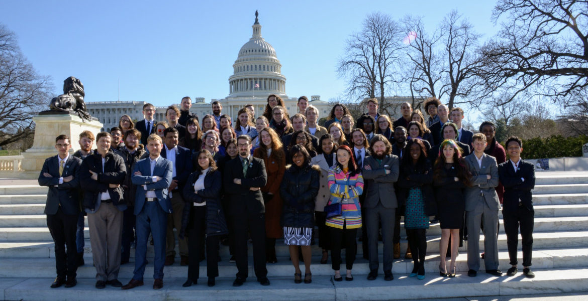 A group of young people in suits with their arms crossed in front of the U.S. Capitol