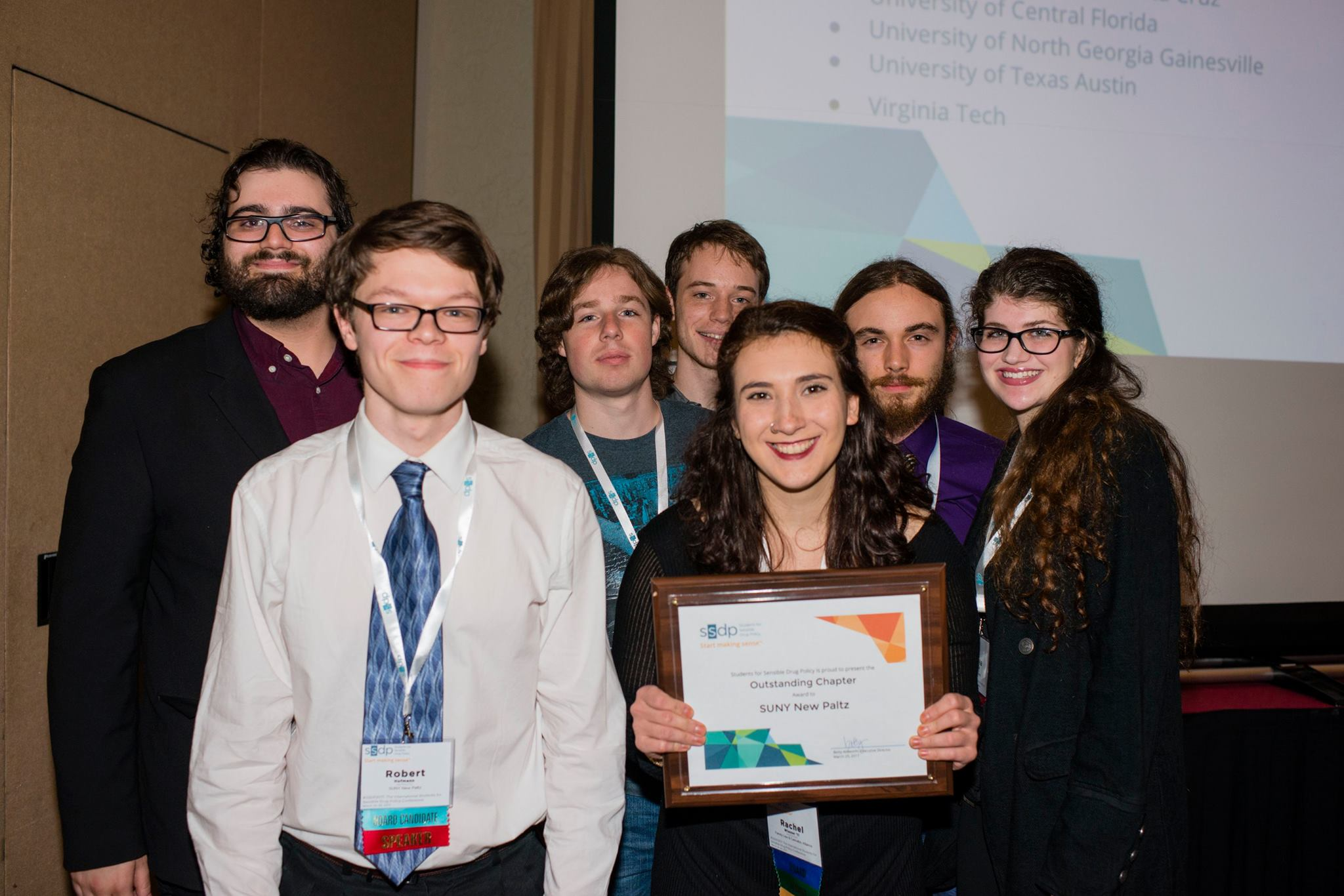Seven young people smiling with an award plaque