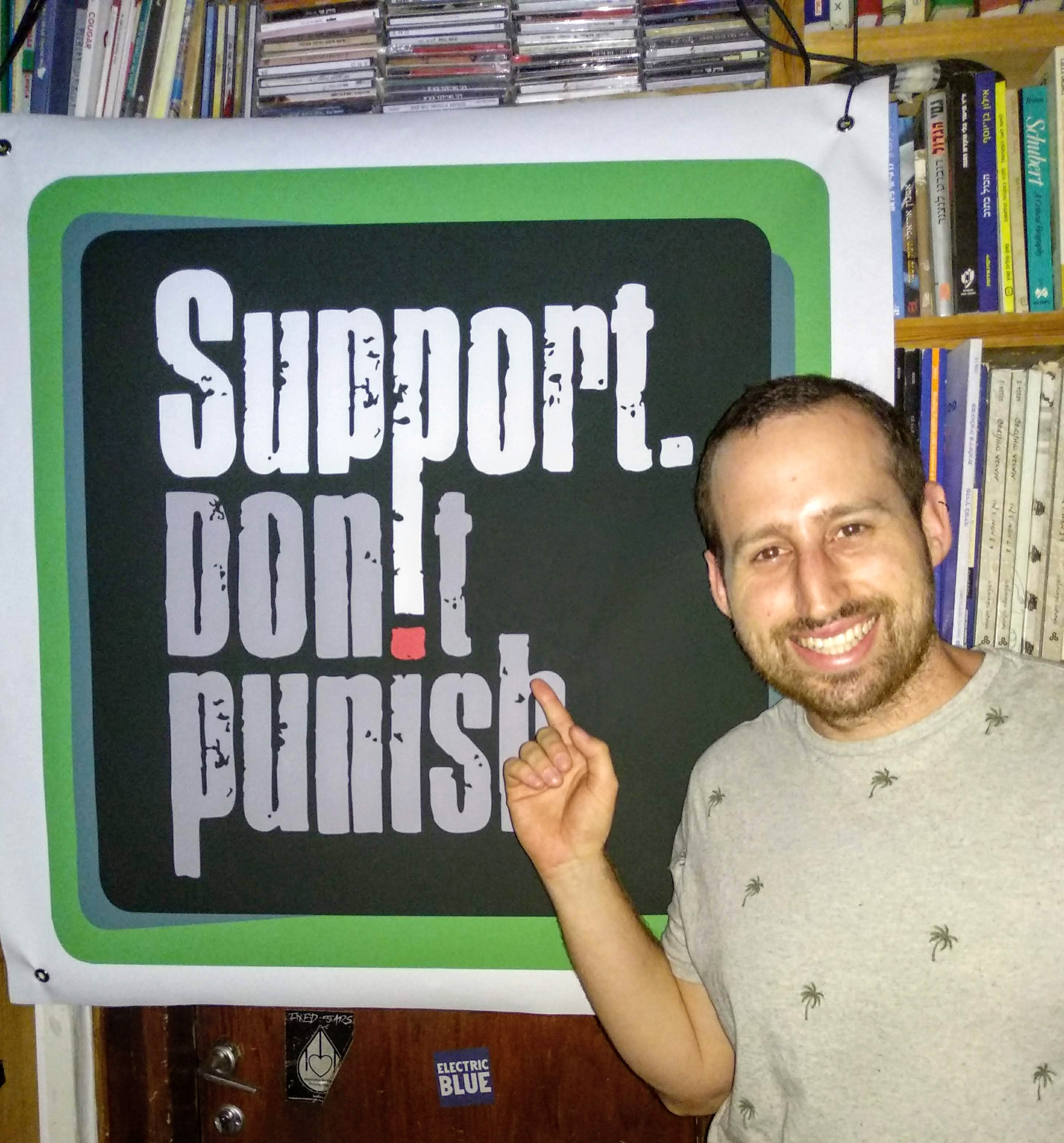 Amit from SSDP Israel standing in front of a Support Don't Punish poster.