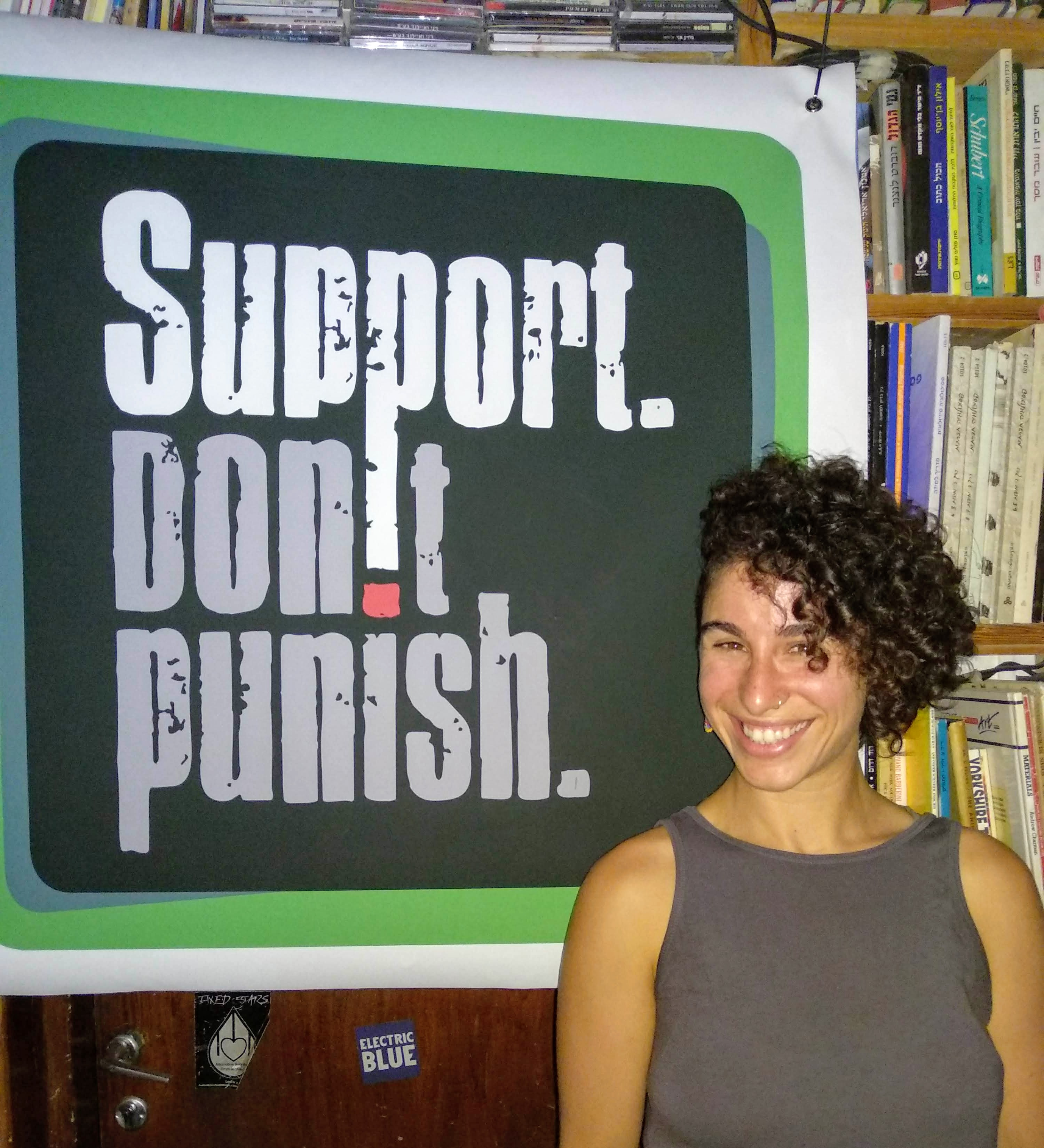 Dovrat from SSDP Israel standing in front of a Support Don't Punish poster.
