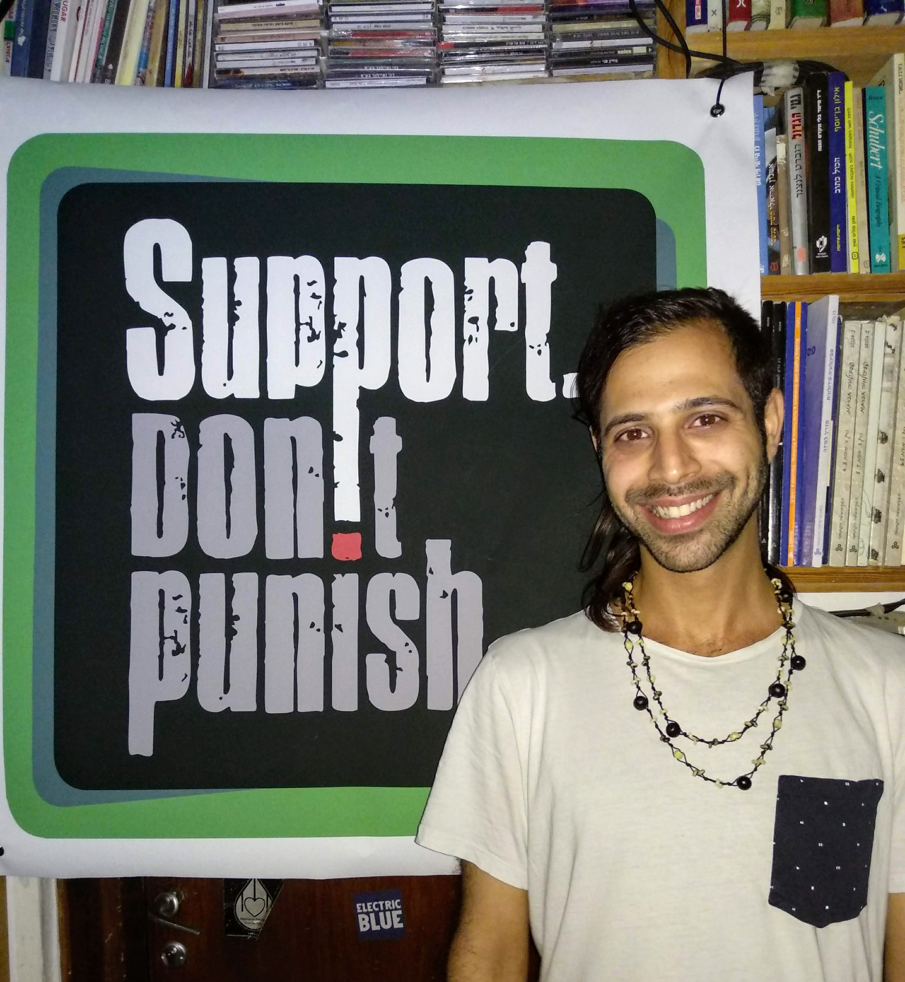 Effie from SSDP Israel standing in front of a Support Don't Punish poster.