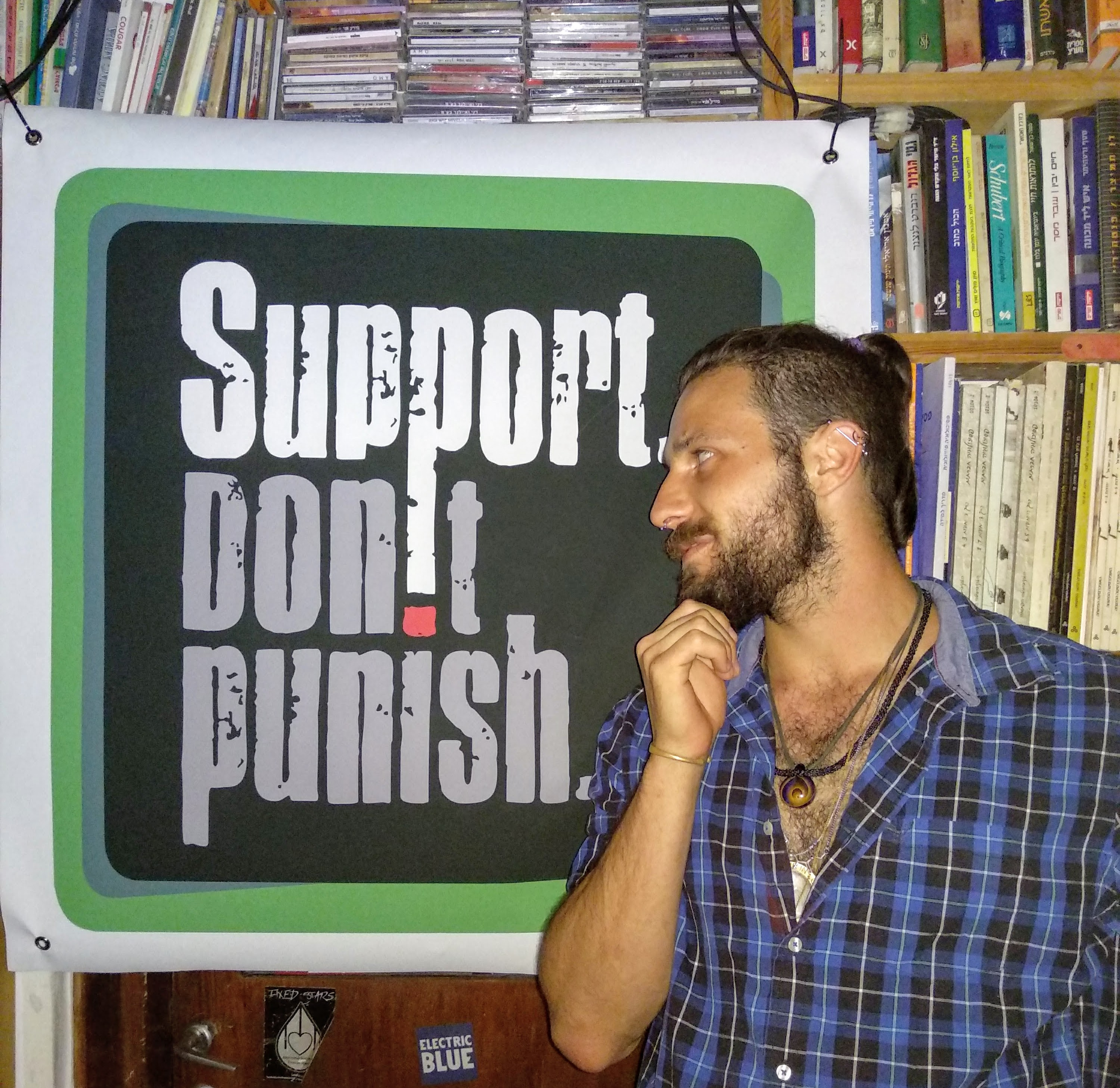 Michael from SSDP Israel standing in front of a Support Don't Punish poster.