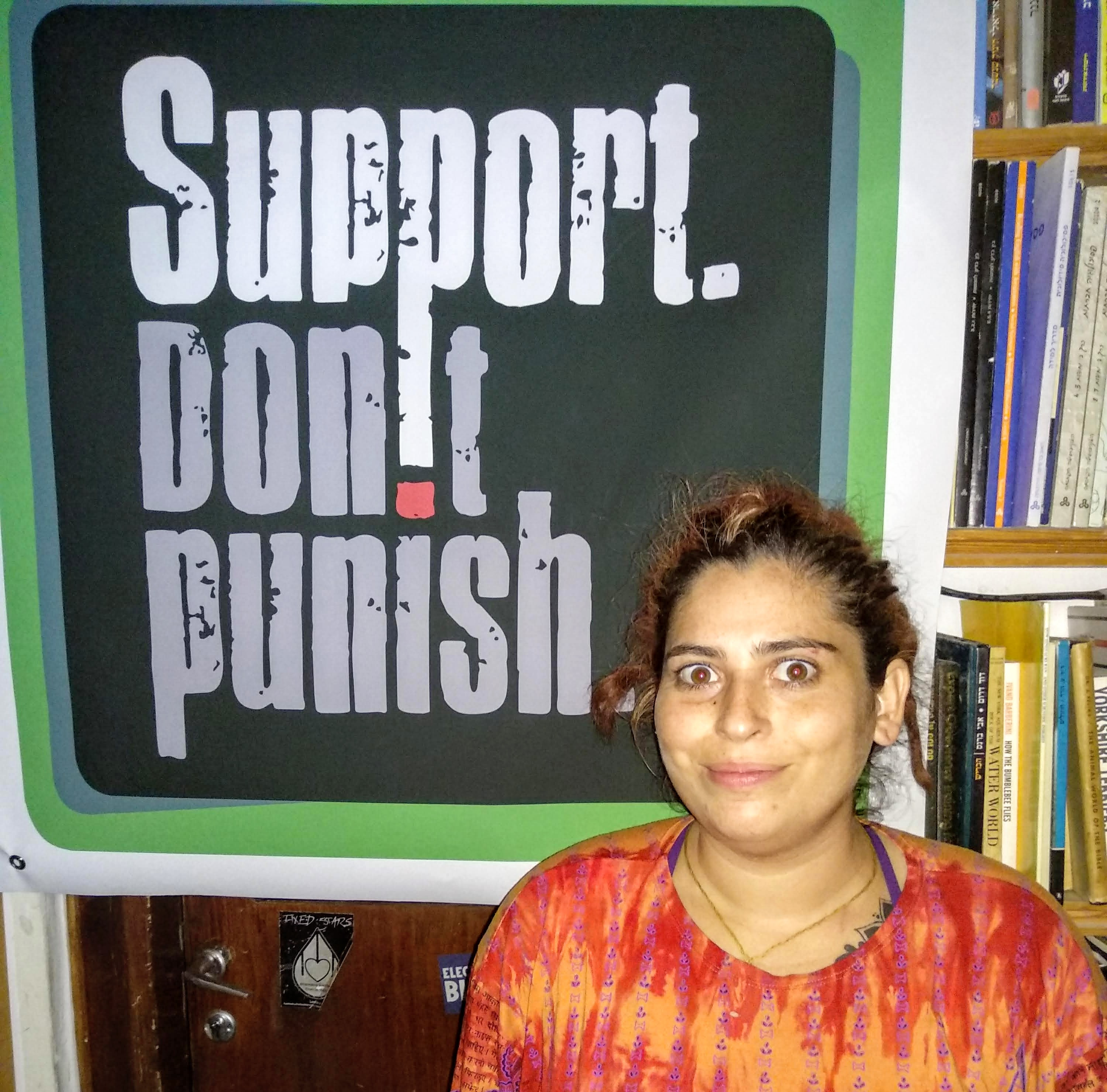 Raquel from SSDP Israel standing in front of a Support Don't Punish poster.