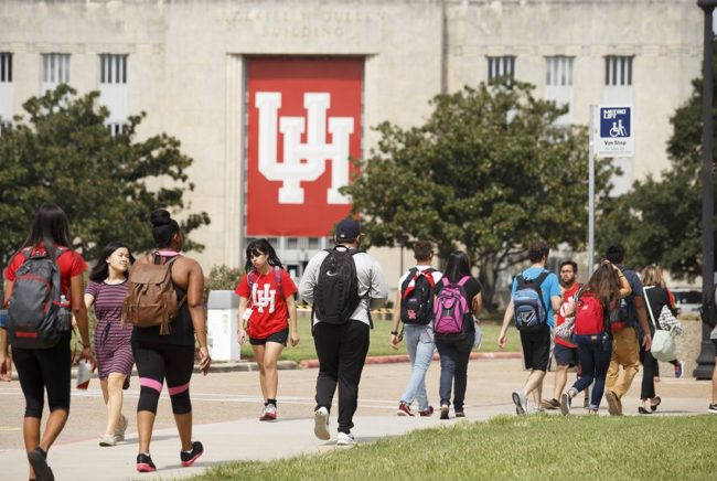Students walking to and from class. the University of Houston logo features prominently on building in the background.