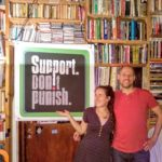 SSDP Israel members Yahav and Amit standing in front of a Support Don't Punish poster.