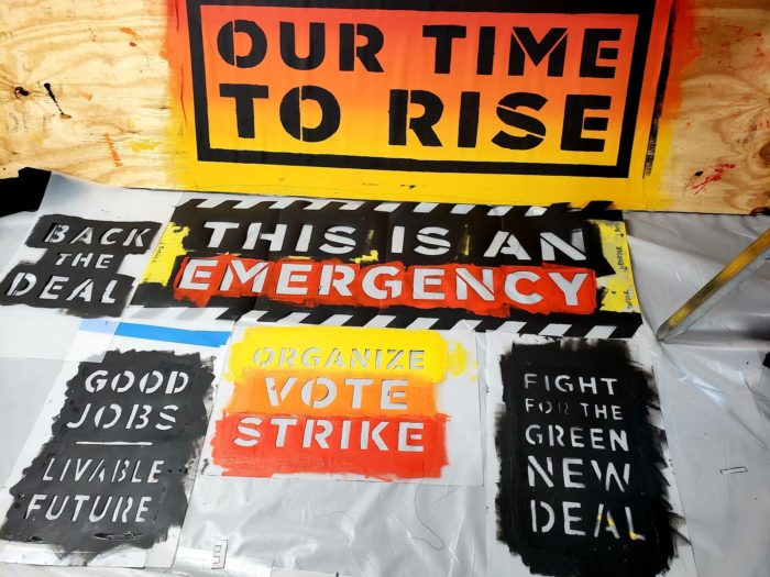 "Picture of a series of stencils that include such phrases as ""organize, vote, strike"", ""Fight for the Green New Deal"", ""Good Jobs - Liveable Future"", ""this is an emergency"", ""back the deal"", and ""Our Time to Rise"""
