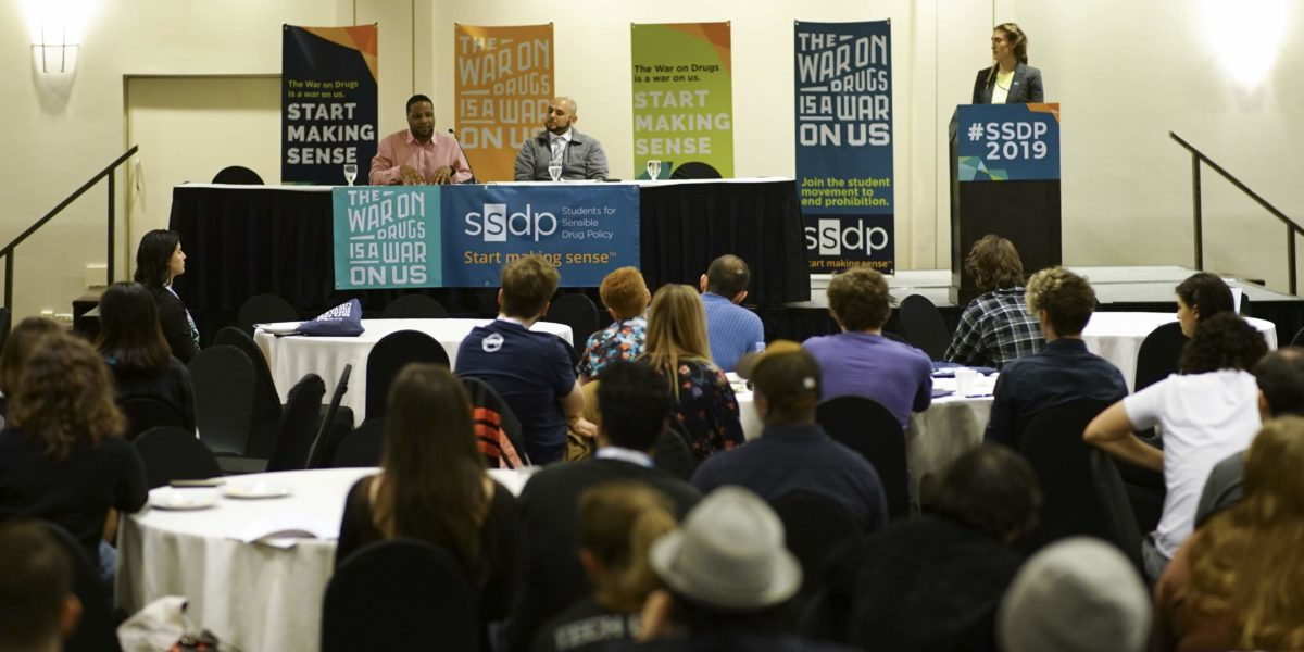 Two men speaking from a stage with colorful SSDP banners, a young person at the podium, speaking to an audience