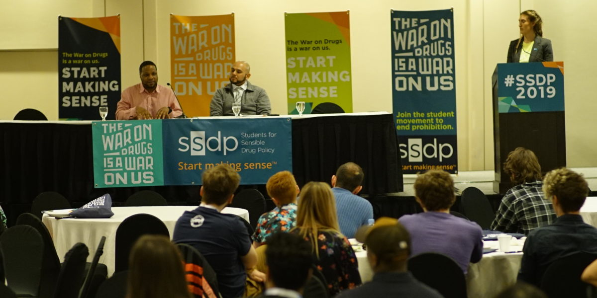 3 people on a stage in front of colorful SSDP banners speaking to an audience