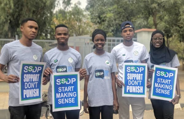 group of five people stood holding signs that read SSDP Support Don't Punish and SSDP Start Making Sense