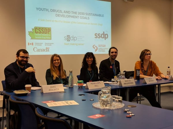 group of five people seated at a table, with logos of drug policy organizations behind them. Name tags read: Jake Agliata, Penelope Hill, Nazlee Maghsoudi, Alex Betsos (the nametag of the fifth person, Orsi Fehér, is out of frame)